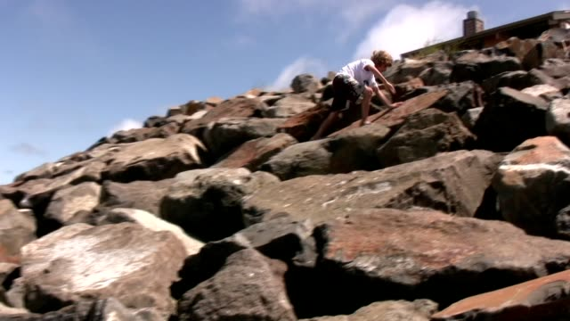 adventurous boy climbing rocks video
