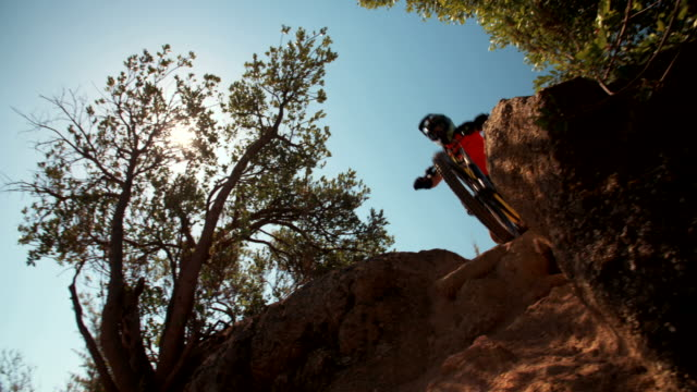 Adventurous mountain biker going over rocks on an off-road trail video