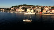 Aerial: a sailboat coming back to harbor at sunset, Mali losinj video