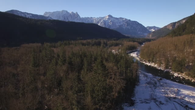 Aerial Above River in Winter Snow Dusted Mountain Forest on Sunny Day video