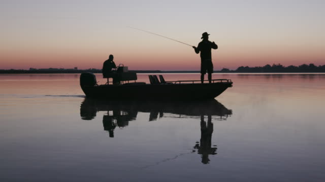 Aerial backlit view of Fisherman fly fishing from a boat video