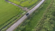Aerial: Black SUV car driving along green fields video