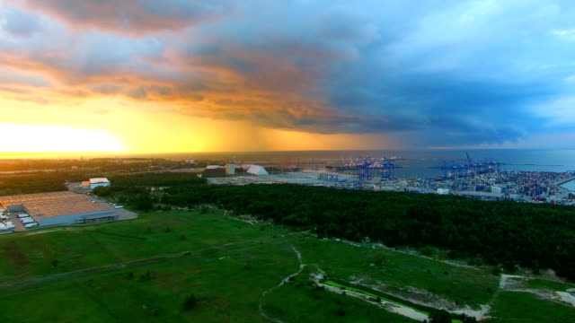 Aerial container ship terminal thunderstorm clouds sunset video