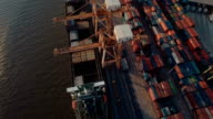 Aerial Crane loading cargo containers in freight ship video