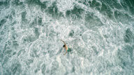 Aerial directly above footage of the young man walking in the surf and getting hits by the waves. video