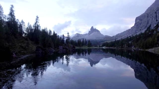 Aerial drone flight establisher over lake with evening clouds and forest.Summer adventure journey in mountain nature outdoors. Travel exploring Alps, Dolomites, Braies, Italy. 4k video side video