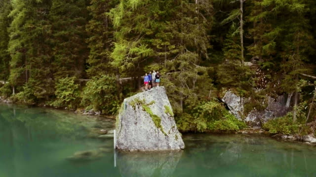 Aerial drone flight over group of friends people looking at lake.Summer adventure journey in mountain nature outdoors. Travel exploring Alps, Dolomites, Braies, Italy. 4k video orbit video