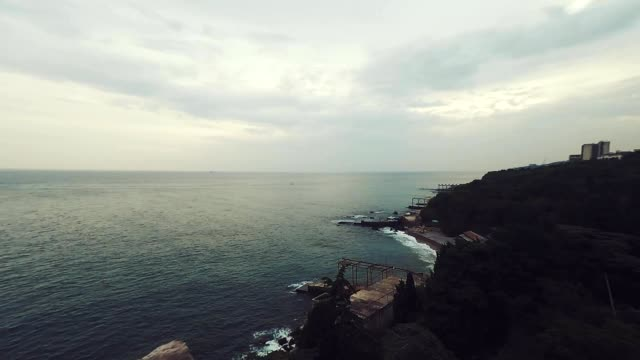 Aerial drone shot: Flying over tranquil sea with cloudy sky in the background video