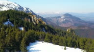 Aerial drone shot in mountain area of Ciucas alpine range , middle Carpathians, Romania, showing snowy peaks, untouched and widespread fir forests and spectacular precipices over limestone rock formations , at beginning of spring video