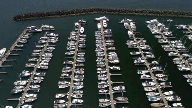 Aerial Drone Shot of Boating Season with Big Expensive Boats Docked at Ocean Marina on Sunny Day video