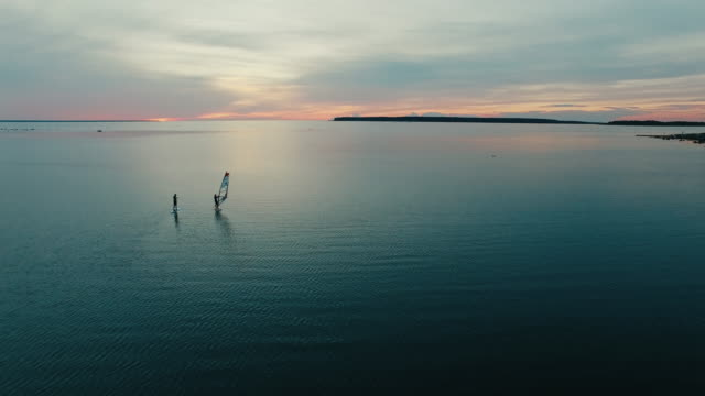 Aerial drone shot of windsurfer and paddleboarder at sunset. video