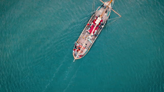 Aerial drone shot over the mast of a sailing boat in the sea. video