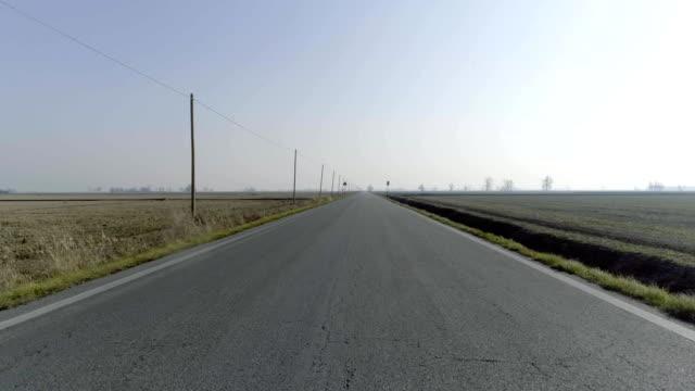 aerial empty paved road in rural fields. forward follow 4k drone video video