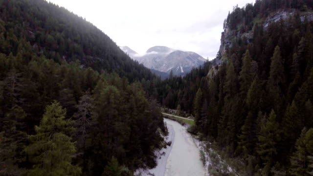 Aerial flight above river creek with woods and rocks in sunny day. Summer adventure journey in mountain nature outdoors. Travel exploring Alps, Dolomites, Italy. 4k drone backward video video