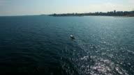 Aerial flight over sailboat at Black Sea, city coastline on the background video