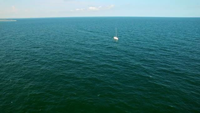 Aerial flight over sailboat at sea video