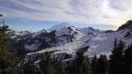 Aerial Fly Through Tree Frame to Snowy Mountain Range with Mt Baker on Sunny Day video