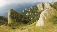 Aerial flying along high altitude mountain peaks with steep cliffs and coniferous trees in the valley below video