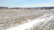 Aerial flying over corn field and backroad covered in snow video