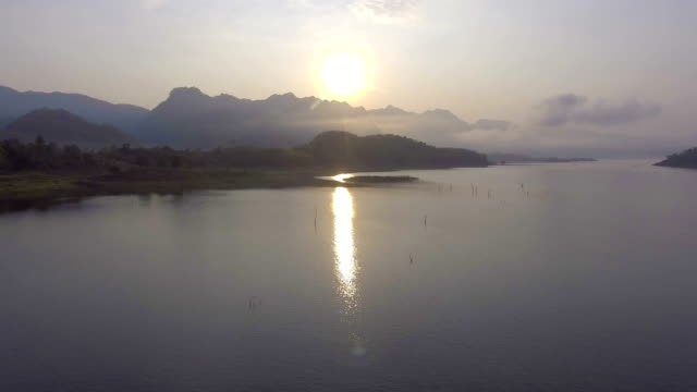 Aerial footage : Amazing shot of beautiful sunrise on a lake with fog on the mountain video