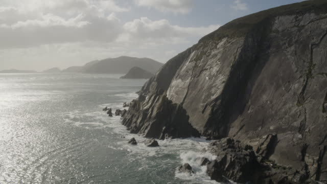 Aerial Footage Of Sea And Rocky Mountains Against Cloudy Sky video