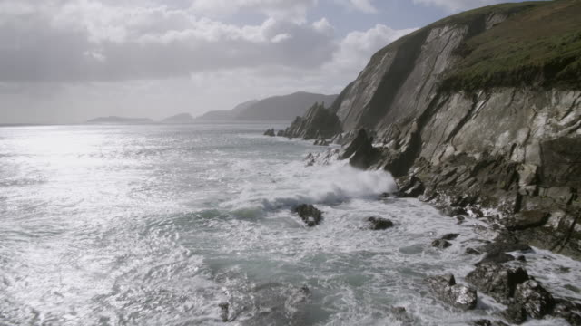 Aerial Footage Of Waves Breaking On Rocky Mountains Against Cloudscape video