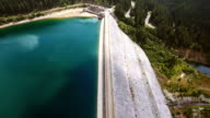 Aerial footage over the dam of lake at mountain in summer video