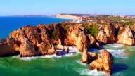 Aerial from rocks and ocean at Ponte de Piedade in Lagos Portugal video