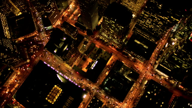 Aerial night vertical view of skyscraper rooftops, USA video