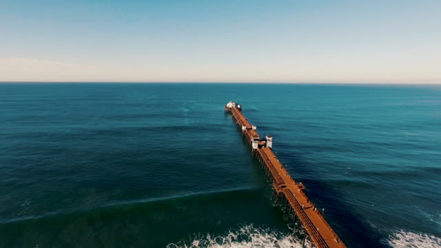 Aerial of a beautiful sunrise sparkling off the ocean as the pier seems to go on forever into the blue abyss. video