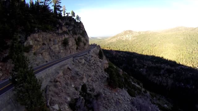 Aerial of car driving along the mountain road. Forest village beautiful summer sunset sunrise trees. Hills travel rural hilly winter scenery car driving countryside road snow clouds sky sunlight video
