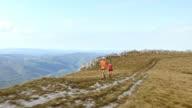 Aerial of couple running on the mountain ridge video