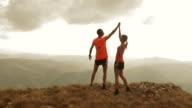 Aerial of couple running to mountain top and raising hands video