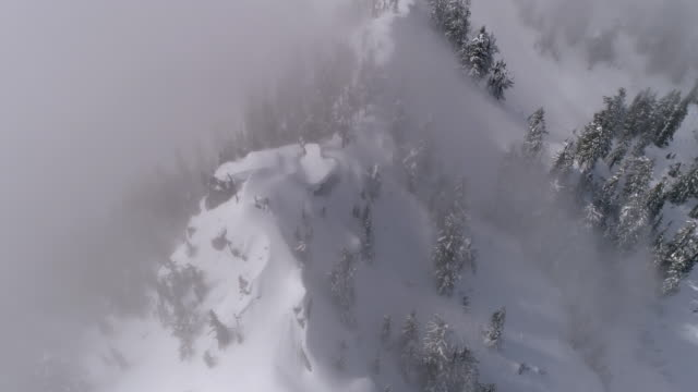 Aerial of Hazy Snow Covered Mountain Ridge Panning to Sky Above Fog Clouds video