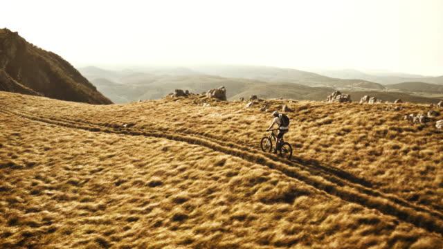 Aerial of mountain biker riding the ridge in morning sun video