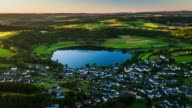 Aerial of rural landscape with village next to a lake - Schalkenmehrener Maar in Germany video
