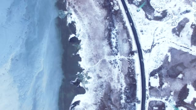 Aerial of suburban road and frozen sea in winter video