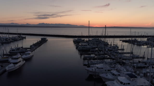 Aerial of Sunset on Ocean Marina with Luxury Boats Docked and Mountain Background video