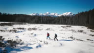 Aerial of winter mountaineers walking across mountain valley video
