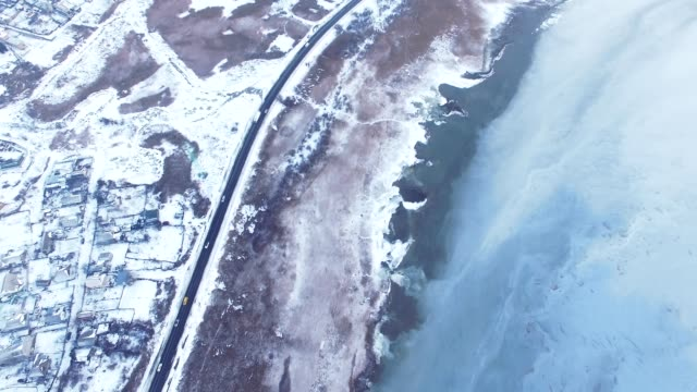 Aerial of winter road and frozen lake video