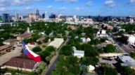 Aerial: Over Austin Texas Capital Cities with Texas Flag with Skyline Cityscape background with Frost Bank Tower and Austonian video