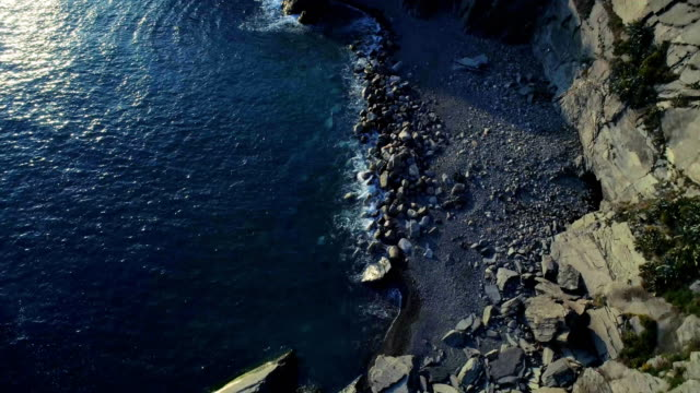 aerial overhead view of ocean mediterranean sea waves reaching and crashing on rocky shore beach, near Cinque terre National Park, Liguria, Italy. Sunny weather. 4k top view drone forward video shot video