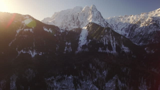 Aerial Pan from Sun Lens Flare on Mountain Top to Snowy Peaks video