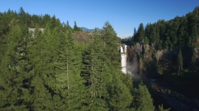 Aerial Pan Revealing Snoqualmie Falls on Sunny Day and Mount Si in Background video