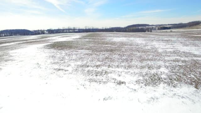 Aerial rolling farm lands covered in snow video