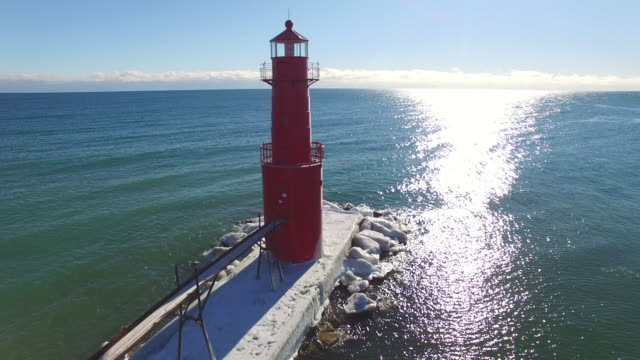 Aerial rotation view of beautiful red lighthouse in icy harbor video