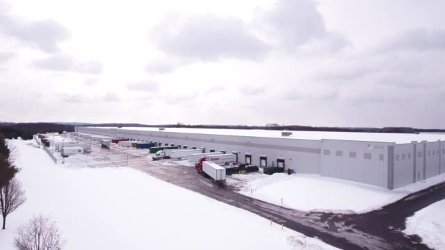 Aerial Semi truck filling up at warehouse in the snow video
