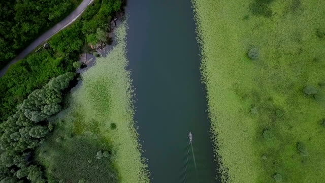 Aerial shooting river with lilies and boat in water surface flowing around hill. video