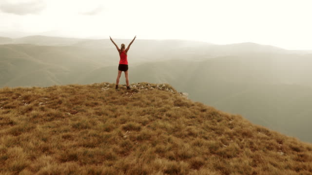 Aerial shot female runner on top of mountain raising hands video