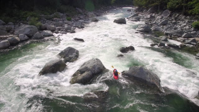 Aerial Shot Following Young Woman in Kayak Down River with White Water Rapids video